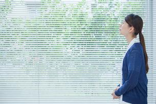 窓際で空を見上げる看護師の横顔の写真素材 [FYI02068860]
