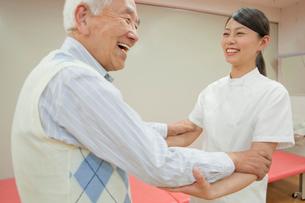 リハビリ施設でシニア男性を介助する女性介護士の写真素材 [FYI02068866]