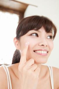 頬にスキンクリームを塗る若い女性の写真素材 [FYI02068868]