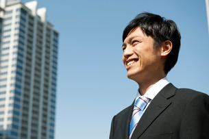オフィス街で笑顔のビジネスマンの写真素材 [FYI02068874]