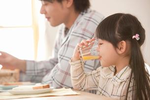 朝食でオレンジジュースを飲む女の子の写真素材 [FYI02068875]