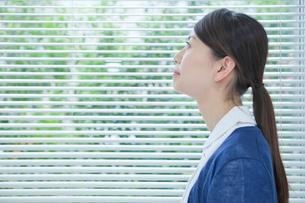 窓際で空を見上げる看護師の横顔の写真素材 [FYI02068898]