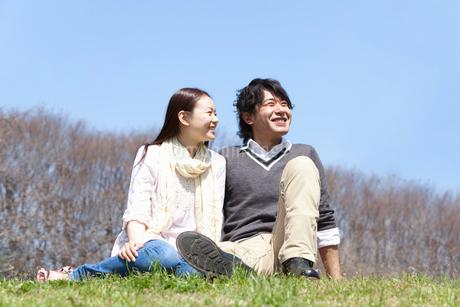公園の芝生の上に腰掛けるカップルの写真素材 [FYI02068899]