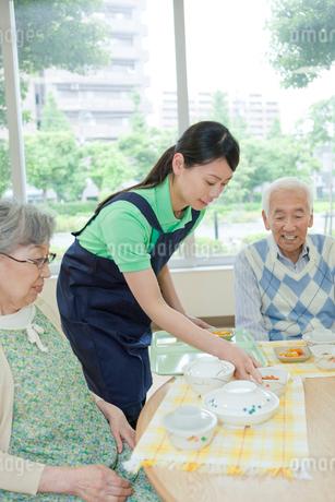介護施設でシニア女性に食事を配膳する女性介護士の写真素材 [FYI02068902]