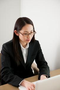 オフィスでノートPCを使い仕事をしている眼鏡の女性の写真素材 [FYI02068904]