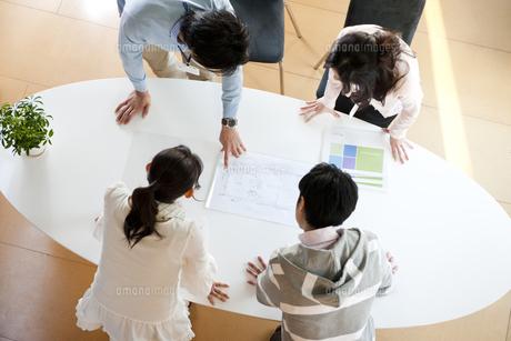 オフィスのミーティングテーブルで打合せをする4人の男女の写真素材 [FYI02068908]