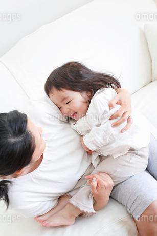 ソファで母親に抱かれる幼児の写真素材 [FYI02068911]