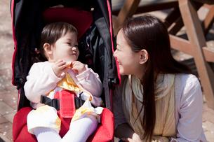 ベビーカーに乗った赤ちゃんに話しかける若い母親の写真素材 [FYI02068925]