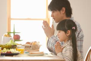 朝食時にいただきますをする娘と若い父親の写真素材 [FYI02068930]