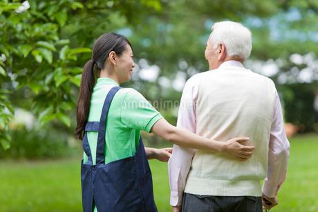 シニア男性と公園を散歩する女性介護士の写真素材 [FYI02068931]