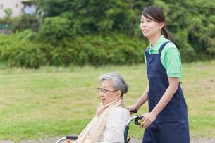 シニア女性の乗った車いすを押す女性介護士の写真素材 [FYI02068933]