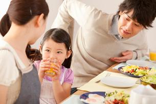 会話をしながら朝食をとる娘と若い夫婦の写真素材 [FYI02068939]