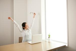 仕事の途中に伸びをして休憩する女性の写真素材 [FYI02068948]