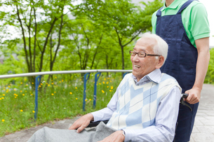 公園を散歩する車いすに乗ったシニア男性と男性介護士の写真素材 [FYI02068949]