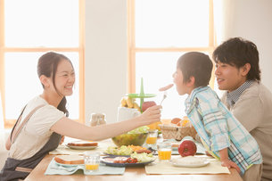 息子にウィンナーを食べさせる母親と見守る父親の写真素材 [FYI02068951]