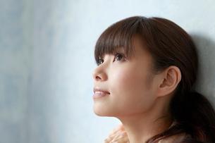 壁に寄りかかり天井を見上げる若い女性の写真素材 [FYI02068955]