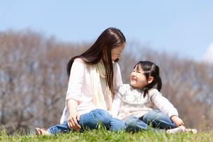 公園の芝生でおしゃべりしている母娘の写真素材 [FYI02068956]