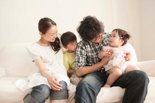 ソファで赤ちゃんを抱く父親を見守る母と息子の写真素材 [FYI02068957]