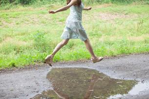 水たまりをジャンプする若い女性の写真素材 [FYI02068961]