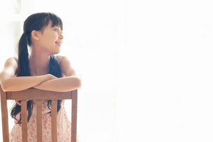 窓際で背もたれに腕を乗せ横を向いた若い女性の写真素材 [FYI02068967]