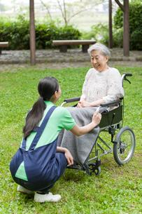 車いすに乗ったシニア女性と話す女性介護士の写真素材 [FYI02068985]