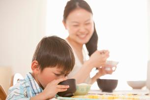 みそ汁を飲む息子を笑顔で見守る母親の写真素材 [FYI02068990]