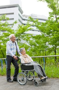 公園を散歩する車いすに乗ったシニア女性とシニア男性の写真素材 [FYI02068995]