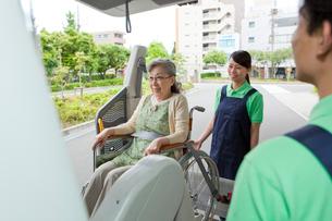 介護車両に車いすの女性を乗せる介護士の写真素材 [FYI02069003]
