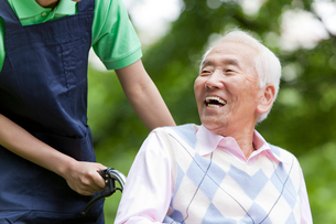 車いすに乗って公園を散策するシニア男性と介護士の写真素材 [FYI02069007]