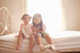 ベッドに並んで座る赤ちゃんと女の子の写真素材 [FYI02069008]