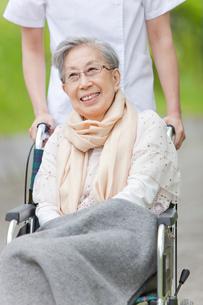 公園を散歩する車いすに乗ったシニア女性と女性介護士の写真素材 [FYI02069009]