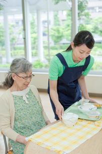介護施設でシニア女性に食事を配膳する女性介護士の写真素材 [FYI02069018]