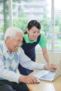 介護施設でノートパソコンを使うシニア男性と女性介護士の写真素材 [FYI02069021]