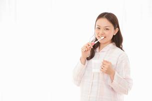 パジャマ姿で歯磨きをする女性の写真素材 [FYI02069027]