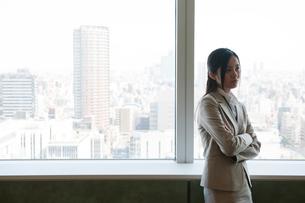 オフィスビルの窓際で腕組みをしているスーツ姿の女性の写真素材 [FYI02069030]