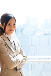 オフィスの窓際で微笑むスーツ姿の女性の写真素材 [FYI02069034]