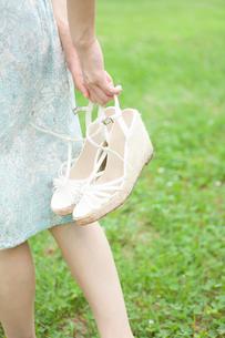 公園でサンダルを手に持ち散歩する若い女性の手元の写真素材 [FYI02069035]