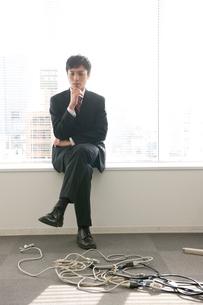窓際に腰掛けて悩むビジネスマンの写真素材 [FYI02069036]