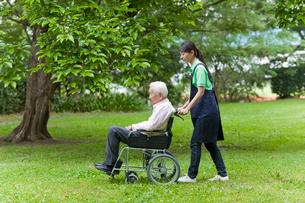 シニア男性の乗った車いすを押す女性介護士の写真素材 [FYI02069038]