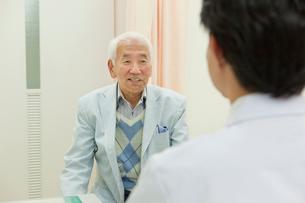 病院の診察室で医師の診断を受けるシニア男性の写真素材 [FYI02069043]