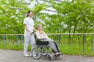 公園を散歩する車いすに乗ったシニア女性と女性介護士の写真素材 [FYI02069046]