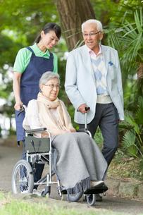 公園を散歩するシニアカップルと女性介護士の写真素材 [FYI02069050]