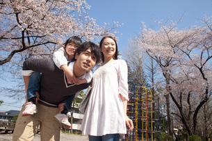 子供を背負う父親と寄り添う母親の写真素材 [FYI02069051]