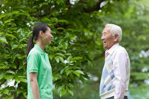 笑顔で向き合う若い女性とシニア男性の写真素材 [FYI02069053]