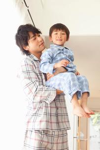 パジャマ姿で子供を抱く若い父親の写真素材 [FYI02069057]