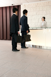 オフィスビルで受付の女性に挨拶をする2人のビジネスマンの写真素材 [FYI02069059]