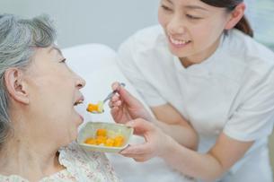 ベッドで横になるシニア女性に食事介助する女性介護士の写真素材 [FYI02069064]