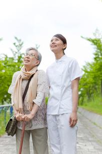 笑顔で空を見上げる女性介護士とシニア女性の写真素材 [FYI02069067]