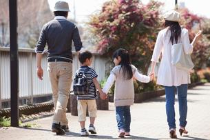 公園で手をつないで散歩する4人家族の写真素材 [FYI02069078]
