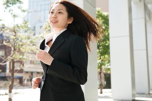 髪の毛をなびかせてオフィス街を走るスーツ姿の女性の写真素材 [FYI02069098]